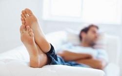 мужчина лежит на диване закинув ноги